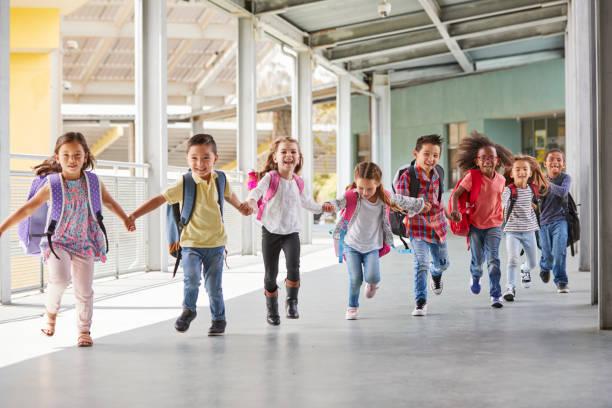 Primary school kids run holding hands in corridor, close up